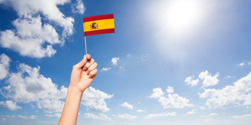Mão do ` s da mulher que mantém a bandeira espanhola contra o céu azul fotos de stock royalty free