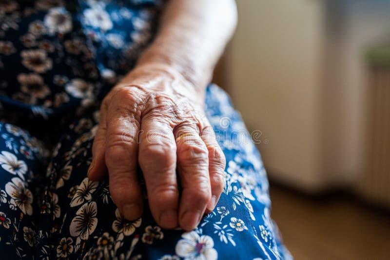 Mão do ` s da senhora idosa com enrugamentos e o ascendente próximo da aliança de casamento imagem de stock
