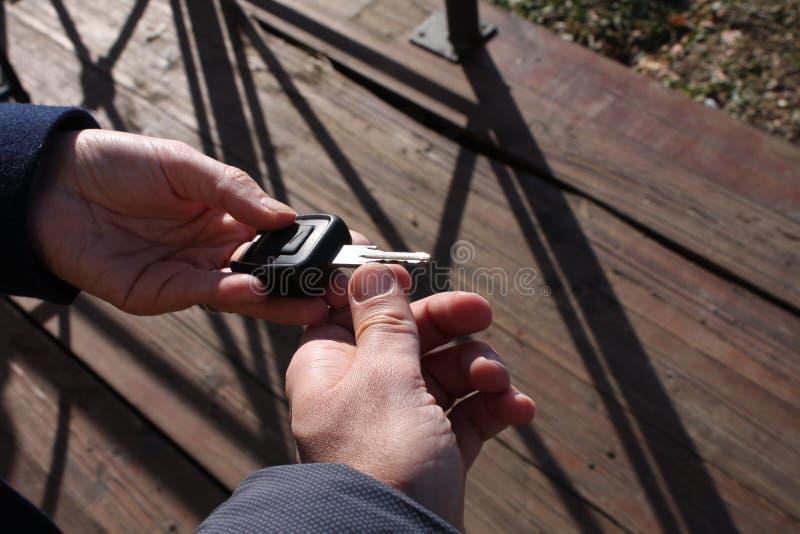 Mão do ` s do comprador que toma uma chave do carro imagens de stock