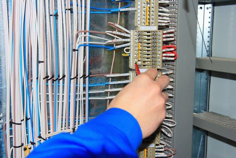 A mão do ` s do eletricista realiza a fiação aos terminais do armário bonde fotos de stock royalty free