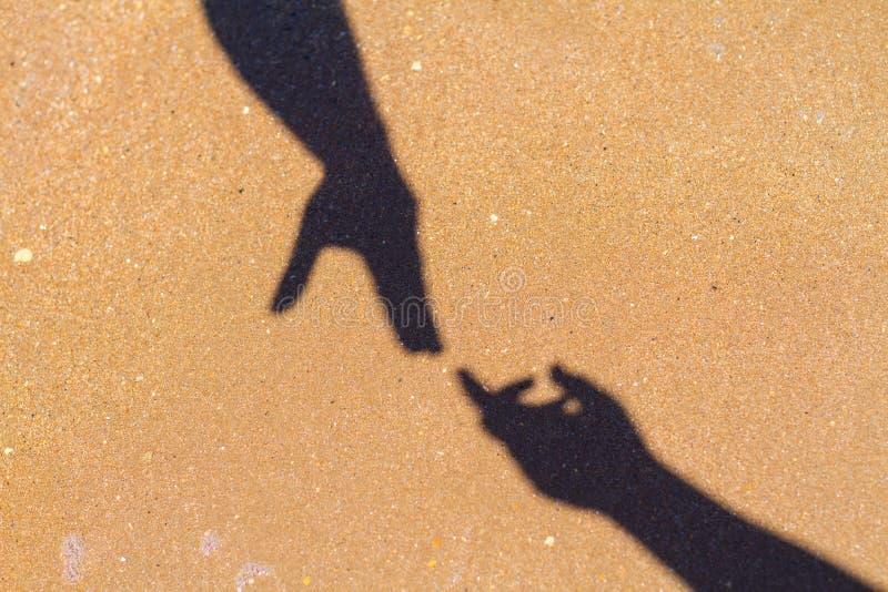 A mão do ` s dos homens alcança para a sombra da mão do ` s das mulheres no fundo da areia foto de stock royalty free