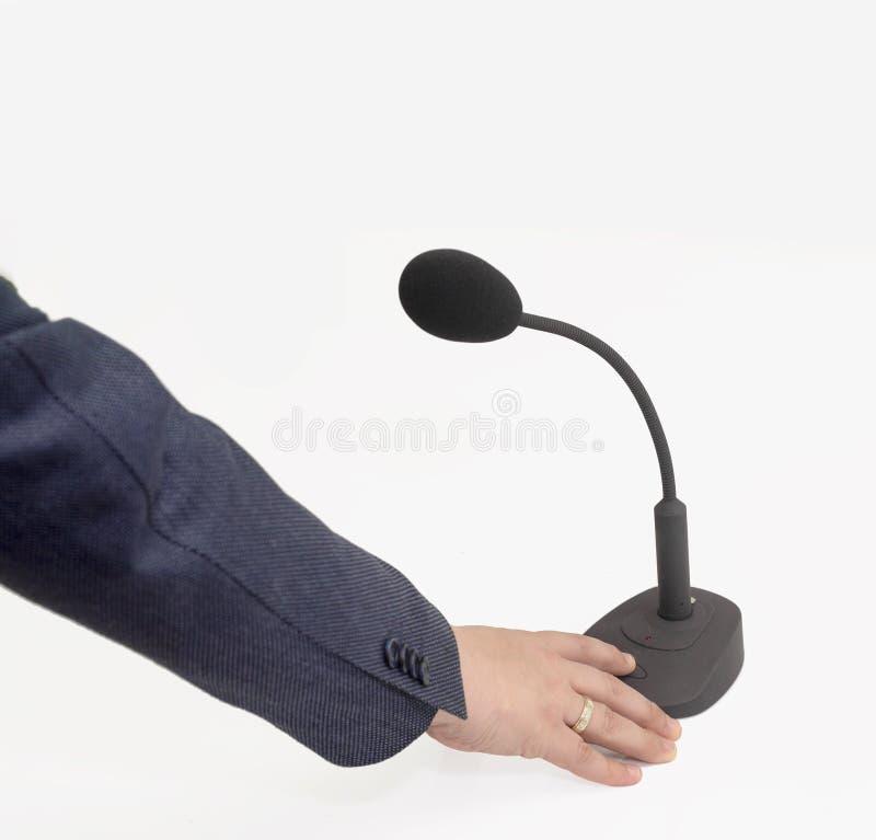 Mão do ` s dos homens em um microfone preto com com suporte e interruptor foto de stock royalty free