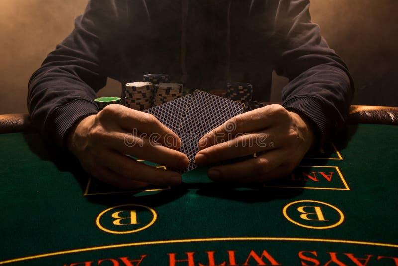 Mão do ` s do homem com cartões de jogo perto acima Microplaquetas do jogo de cartas do casino Põe sobre os cartões de jogo da ta imagens de stock