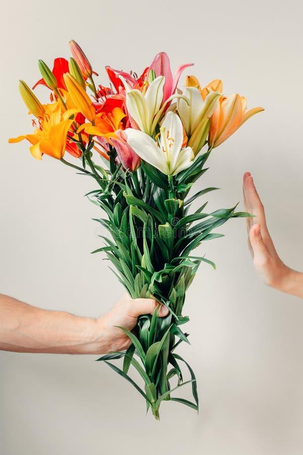A mão do ` s do homem dá o ramalhete de flores dos lírios à menina e recebe a recusa fotos de stock