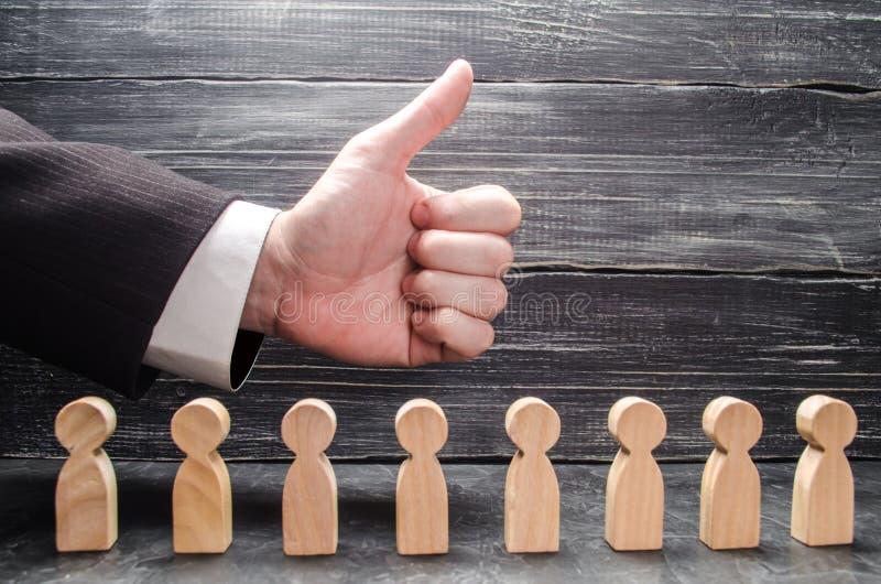 A mão do ` s do homem de negócios mostra os polegares-acima, acima das figuras dos trabalhadores O conceito da aprovação de ideia fotos de stock royalty free
