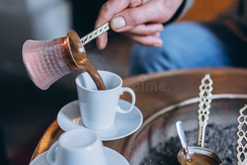 A mão do ` s do homem derrama o café em um copo imagens de stock royalty free