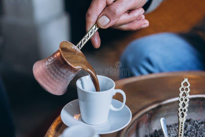 A mão do ` s do homem derrama o café em um copo fotografia de stock royalty free