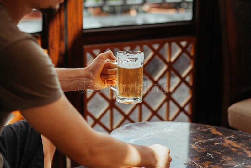 A mão do ` s do homem guarda uma caneca de cerveja Caneca no centro da foto Uma pinta da cerveja clara foto de stock