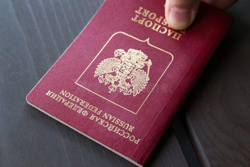 A mão do ` s do homem põe passaportes de um international sobre o fundo de madeira closeup fotos de stock royalty free
