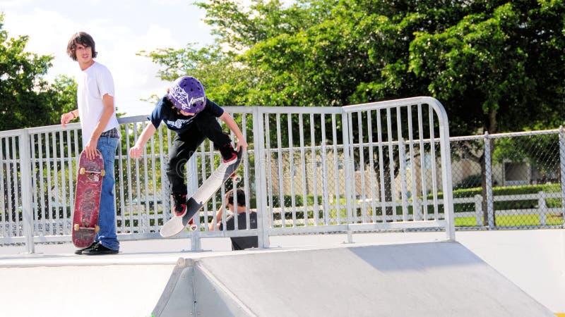 Mão do skater do rapaz pequeno acima foto de stock
