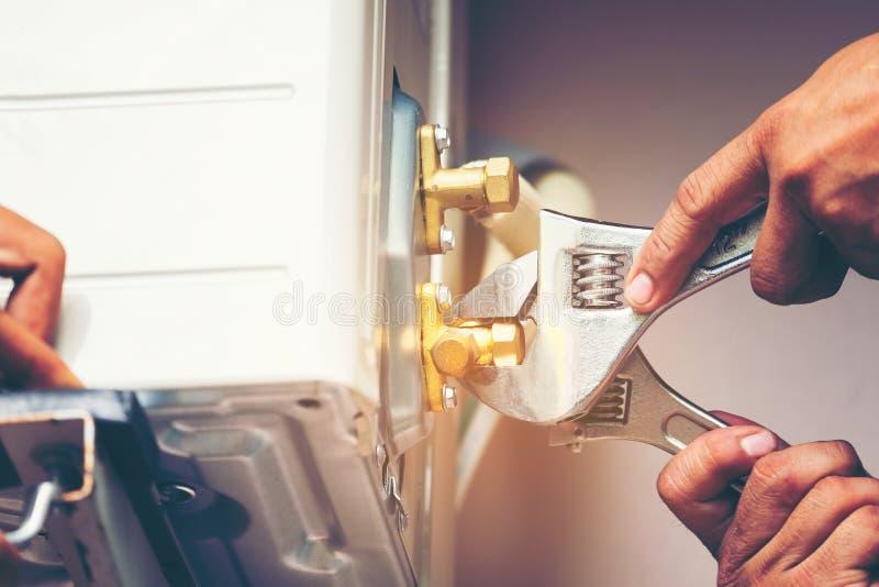 Mão do técnico usando a chave do reparo para apertar a unidade exterior de ar foto de stock royalty free