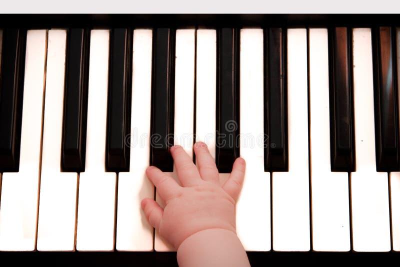 A mão do teclado de piano e da criança pequena imagem de stock royalty free