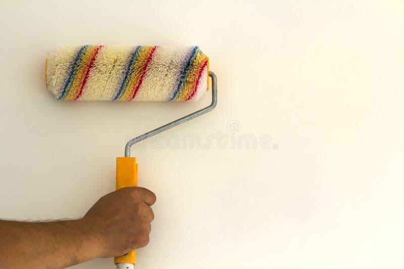 Mão do trabalhador com a escova do rolo de pintura perto da parede no interior renovado da sala isolado no fundo branco Renovação imagens de stock royalty free