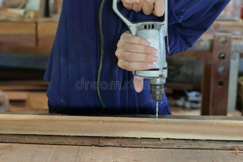 A mão do trabalhador fura um furo com prancha de madeira usando a máquina da broca elétrica na oficina fotos de stock royalty free