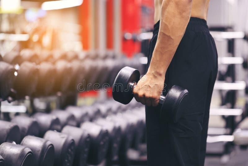 Mão do treinamento do homem que guarda pesos para a gordura da queimadura no corpo no gym do esporte, no estilo de vida saudável  imagens de stock
