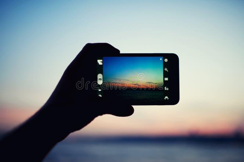 Mão do turista que guarda o telefone celular ao tomar uma fotografia da paisagem da natureza no curso imagens de stock royalty free