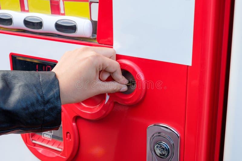 Mão do turista que introduz a moeda com máquina de venda automática da água imagens de stock