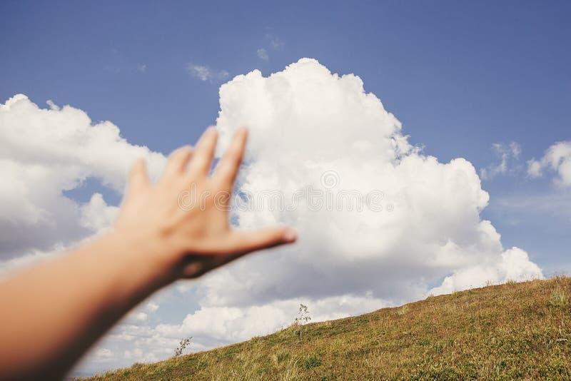 Mão do viajante que alcança para fora às montanhas e às nuvens do céu Foco sobre imagens de stock royalty free