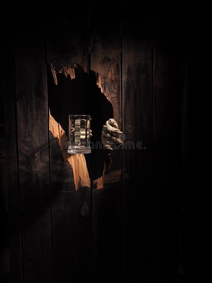 A mão do zombi através do furo rachou-se na madeira rústica Um Web de aranha grande antes de uma lua brilhante estranha fotografia de stock royalty free