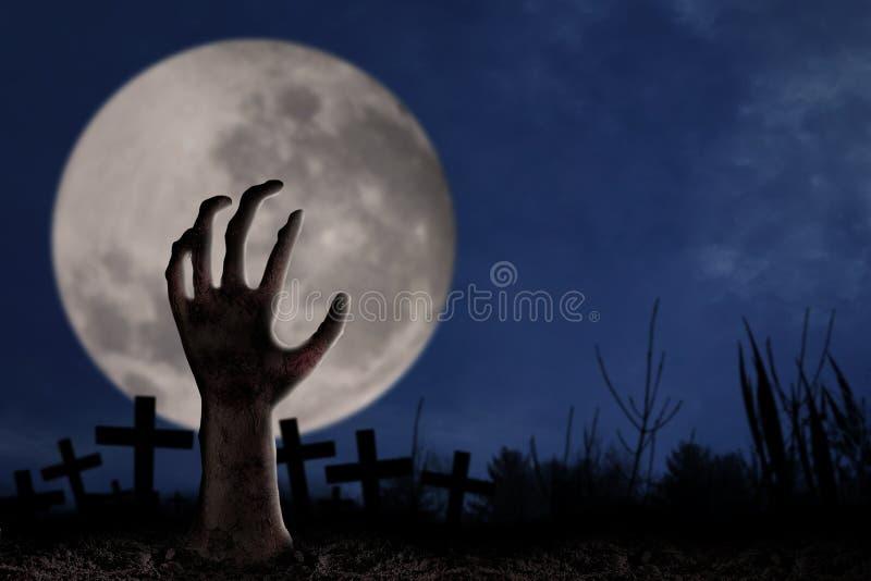 Mão do zombi no cemitério imagem de stock