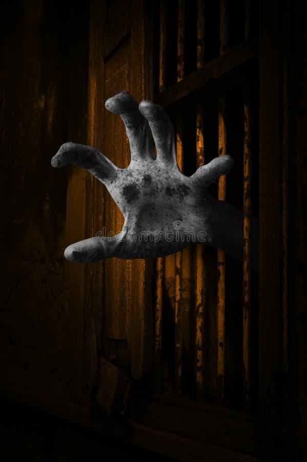 A mão do zombi que aumenta para fora da casa antiga da janela velha, bendiz fotos de stock
