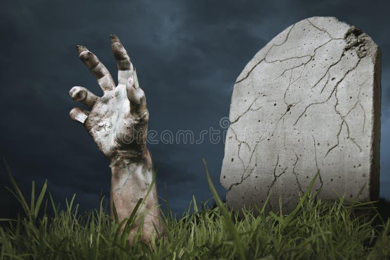 Mão do zombi que sai da terra fotos de stock royalty free