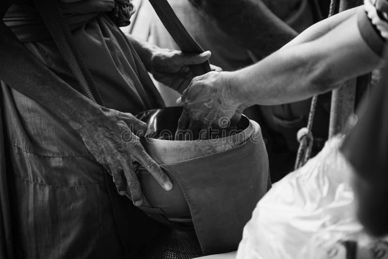 A mão dois do budismo dos povos tailandeses dá a esmola à monge na bacia da esmola, estilo preto e branco da imagem do contraste  imagens de stock royalty free