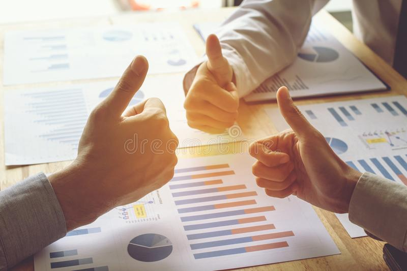 A mão dos executivos está levantando o conceito da equipe do trabalho dos polegares da mão imagem de stock