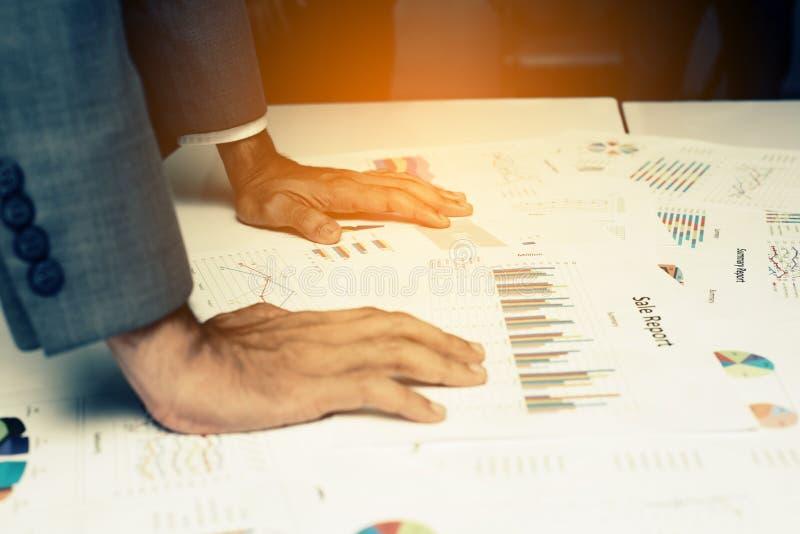 Mão dos executivos novos que analisam o original do gráfico e da carta foto de stock