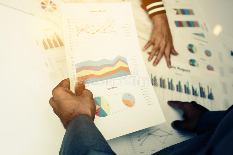 Mão dos executivos novos que analisam o original do gráfico e da carta imagens de stock
