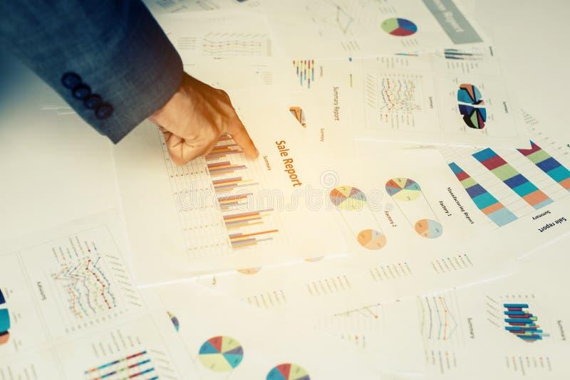 Mão dos executivos novos que analisam o original do gráfico e da carta imagem de stock