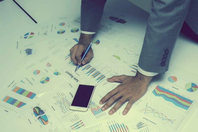 Mão dos executivos novos que analisam o original do gráfico e da carta imagens de stock royalty free