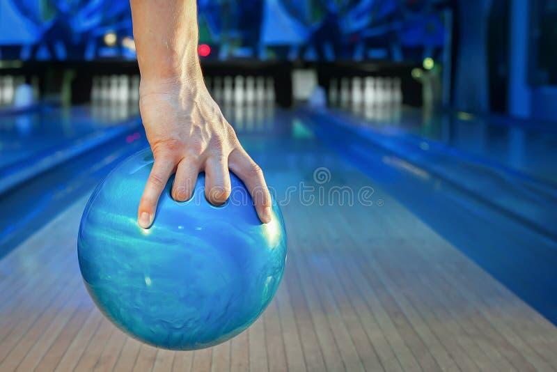 A mão dos homens que guarda uma bola de rolamento azul no fundo do close-up do campo de ação fotos de stock royalty free