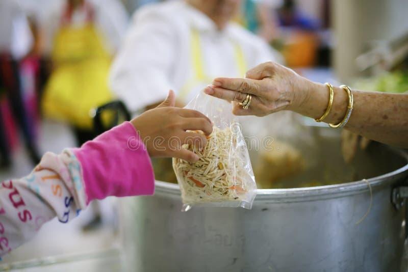 A mão dos mendigos recebe o alimento da caridade dos seres humanos companheiros: o conceito do problema do mendigo na terra imagem de stock