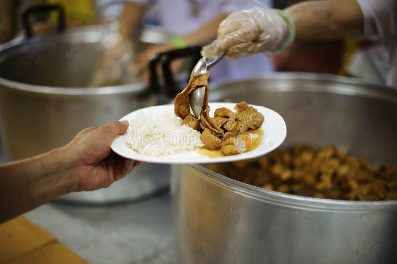 A mão dos mendigos recebe o alimento da caridade dos seres humanos companheiros: o conceito do problema do mendigo na terra imagem de stock royalty free