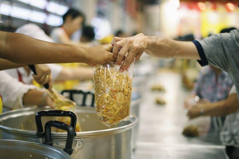 A mão dos mendigos recebe o alimento da caridade dos seres humanos companheiros: o conceito do problema do mendigo na terra fotografia de stock royalty free