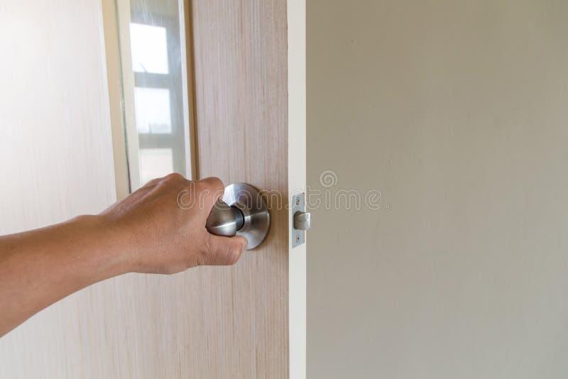 A mão dos povos abre a porta à colocação aberta da porta interna, exterior na porta da rua foto de stock royalty free