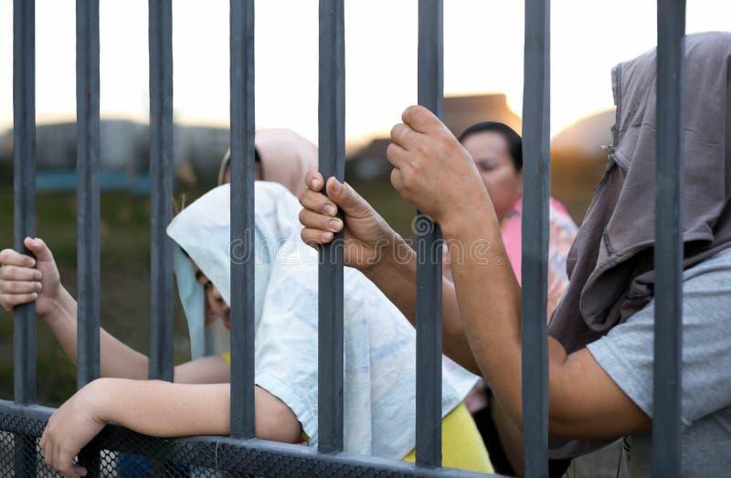 A mão dos povos do refugiado que guarda a barra de metal no local de campo de refugiados senta-se imagem de stock