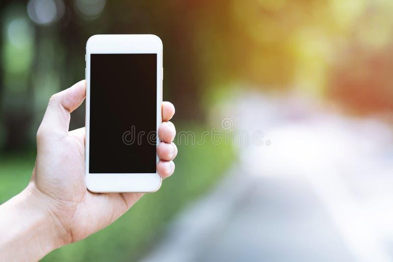 A mão dos povos está guardando o móbil branco da exposição foto de stock