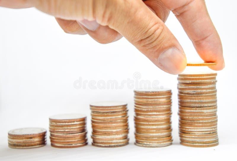 A mão dos povos pôs moedas para empilhar das moedas, investimento de planejadores financeiros, o pulo do investimento, salvar por fotografia de stock