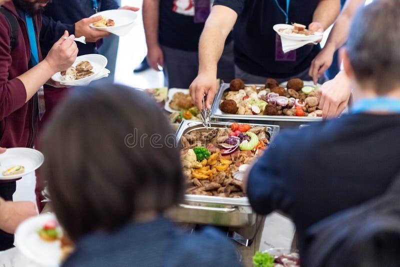 A mão dos povos toma o alimento do bufete no partido do hotel, o alimento e a bebida imagens de stock