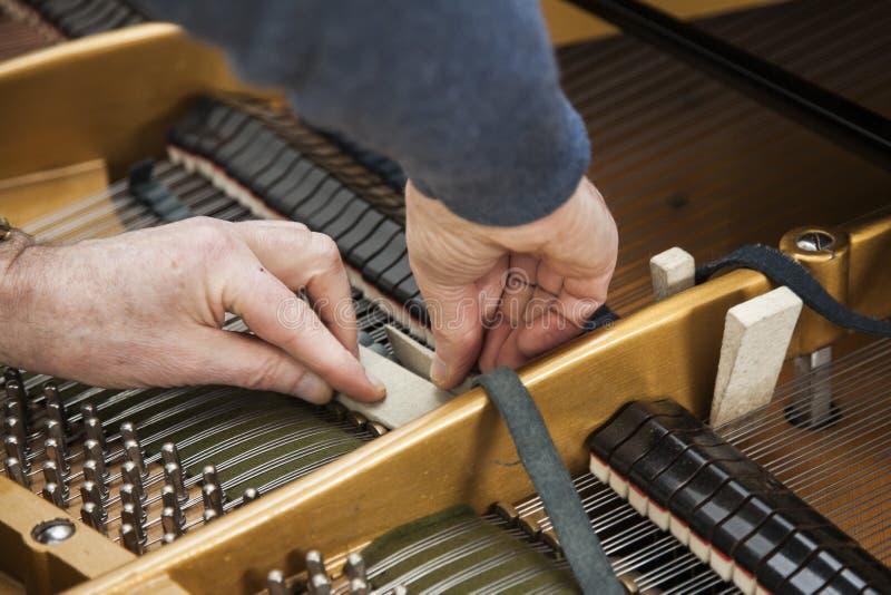Mão e ferramentas do afinador que trabalham no piano de cauda fotografia de stock