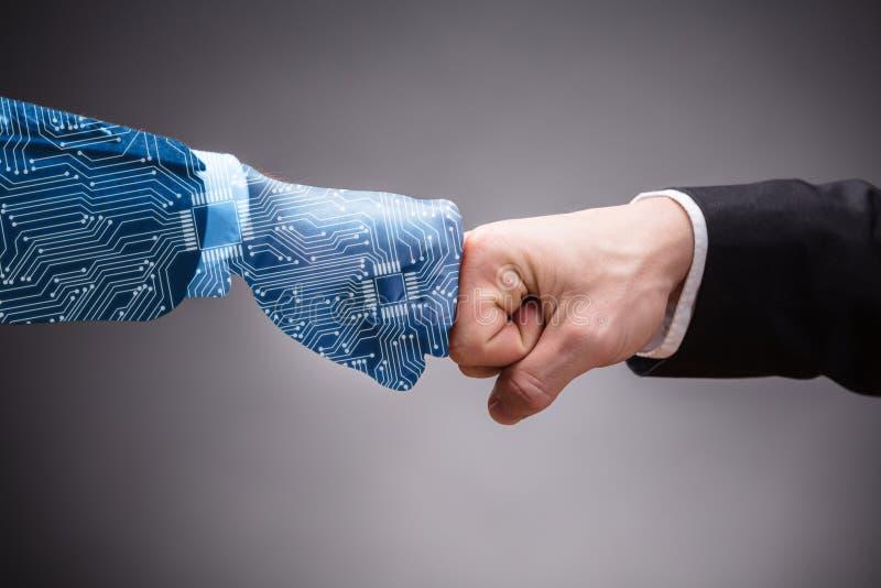 M?o e homem de neg?cios humanos gerados Digitas Making Fist Bump imagem de stock