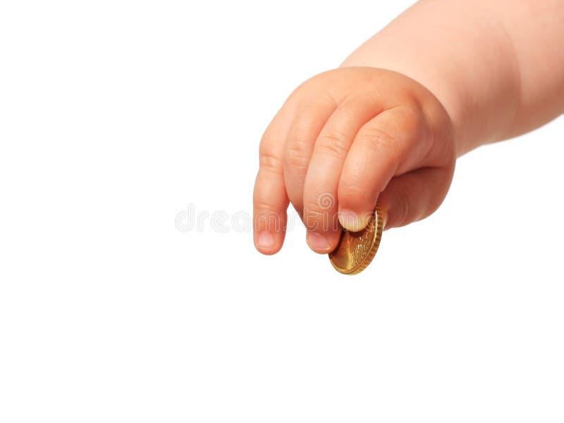 A mão e a moeda do bebê. foto de stock