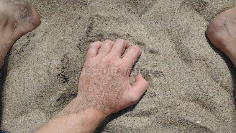 Mão e pés na areia no dia ensolarado da praia foto de stock