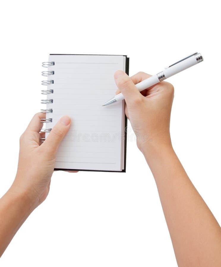 A mão e a pena escrevem no caderno fotografia de stock