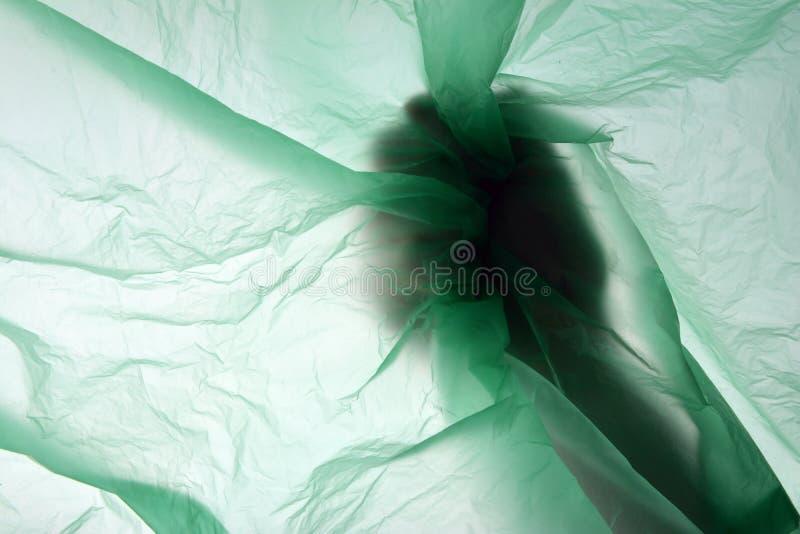 Mão e saco de plástico A mão esmaga o pacote em seu conceito do saco de plástico do punho com espaço da cópia para o texto foto de stock
