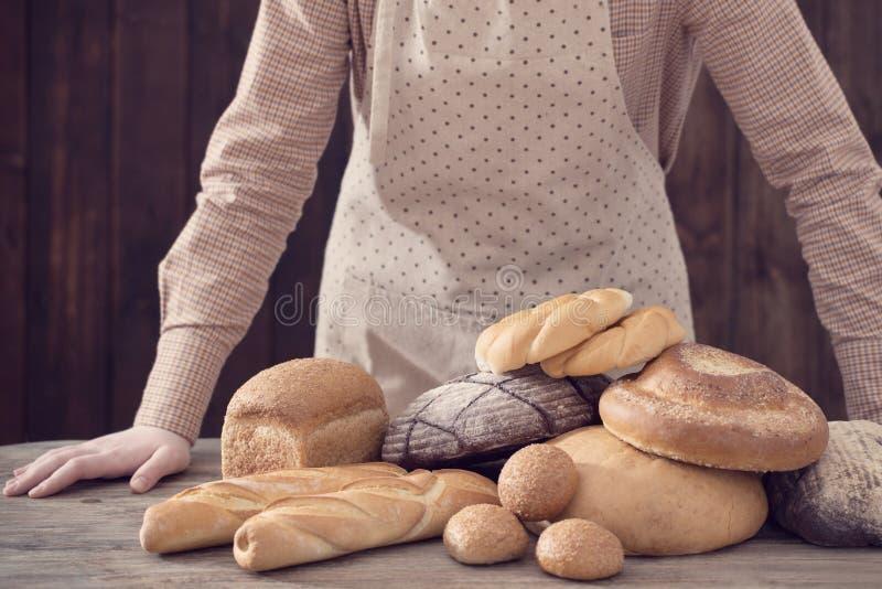 Mão e tipos diferentes de pão no fundo de madeira fotografia de stock