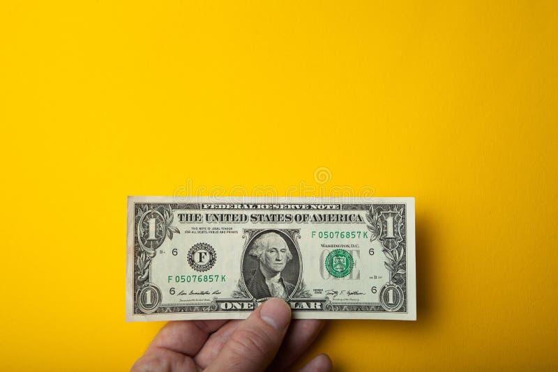 Mão e uma nota de dólar à disposição em um fundo amarelo Espa?o vazio para o texto imagem de stock royalty free