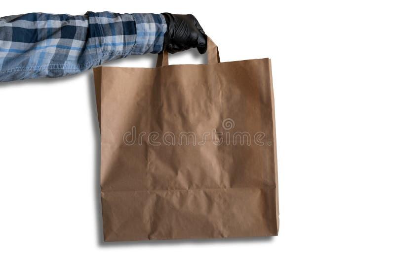 Mão em luvas pretas segura saco de papel em um fundo branco, maquina saco de papel, conceito de entrega imagens de stock royalty free